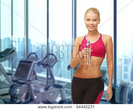 people, sport, fitness and recreation concept - happy woman with bottle of water over gym machines background