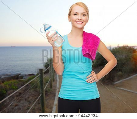 people, sport, fitness, jogging and recreation concept - happy woman with bottle of water and towel over beach sunset background