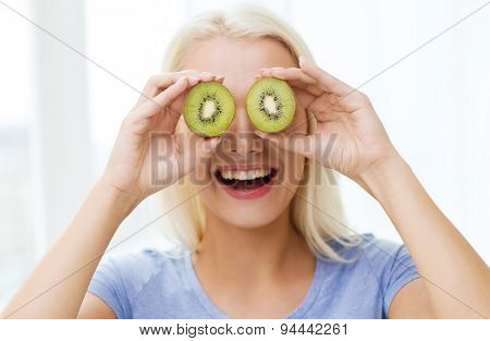 healthy eating, organic food, fruit diet, comic and people concept - happy woman having fun and covering her eyes with kiwi
