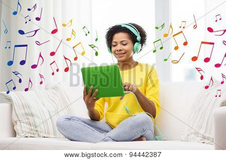 people, technology and leisure concept - happy african american young woman sitting on sofa with tablet pc computer and headphones listening to music at home over notes background