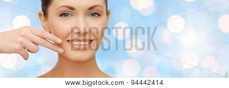 healthcare, people, holidays and beauty concept - beautiful woman touching her face skin over blue lights background