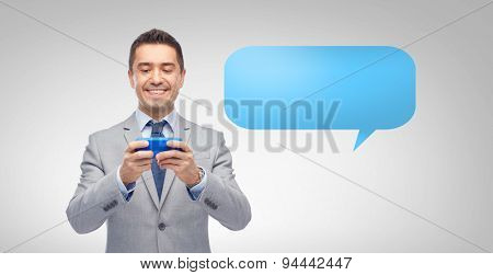 business, people and technology concept - happy businessman texting or reading message on smartphone