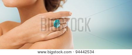 beauty, jewelry, people and accessories concept - close up of woman with cocktail ring on hand over blue background