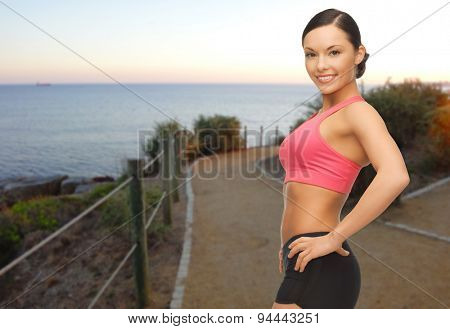 people, sport, fitness and healthy lifestyle concept - happy asian woman jogging outdoors over beach sunset background