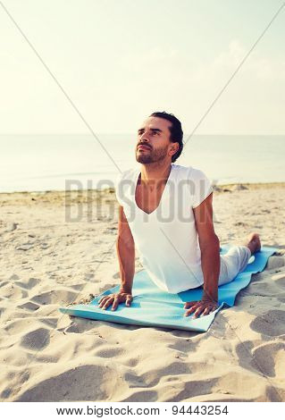 fitness, sport and lifestyle concept - man doing yoga exercises lying on mat outdoors