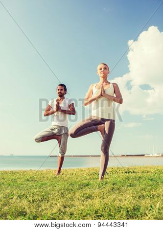 fitness, sport, friendship and lifestyle concept - smiling couple making yoga exercises outdoors
