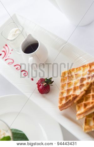 food, dessert, morning and eating concept - close up of waffles on plate at breakfast on table