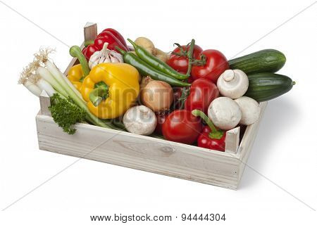 Wooden chest with fresh vegetables on white background