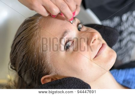 Beautician Trimming A Young Girls Eyebrows
