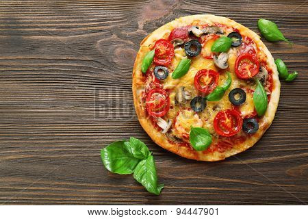 Tasty pizza with vegetables and basil on wooden background