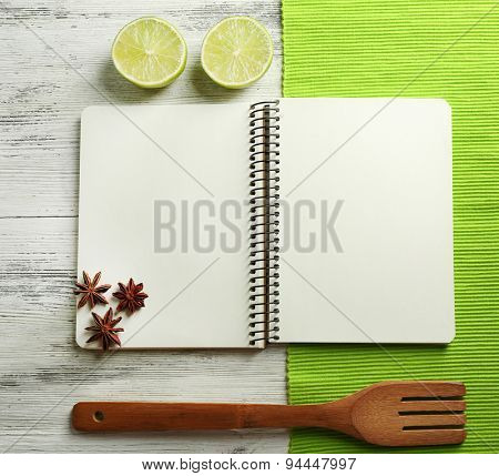 Open recipe book, napkin on wooden background