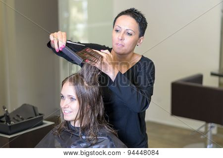 Hairdresser Trimming The Hair Of A Young Woman