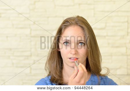 Attractive Young Woman Applying Lipstick