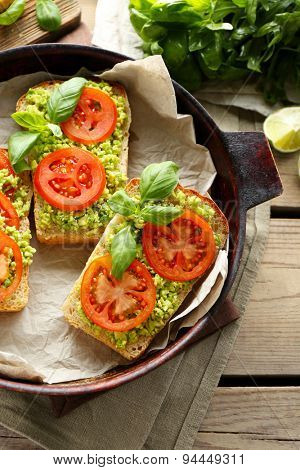 Vegan sandwich with avocado and vegetables on pan, on wooden background