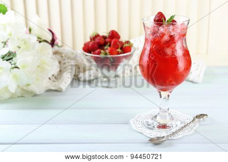 Strawberry dessert with ice in glass, on wooden table, on light background