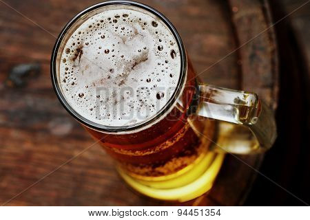 beer glass on wooden barrel