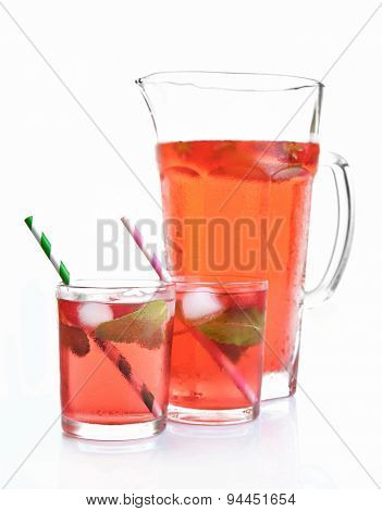Full jug and glasses of strawberry juice isolated on white