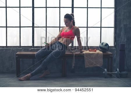 Fit Woman In Loft Gym Sitting On Bench Selecting Music