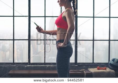 Partial View Of Woman Looking Down At Device Wearing Headphones