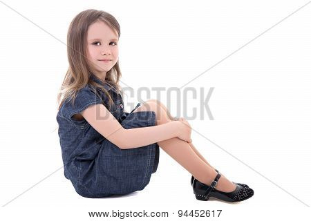 Cute Little Girl In Denim Dress Sitting Isolated On White