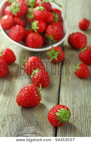 Ripe strawberries in saucer on wooden table, closeup