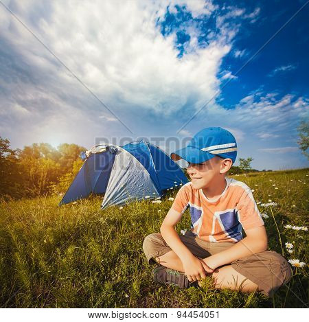 Kid with a tent on a camomile meadow