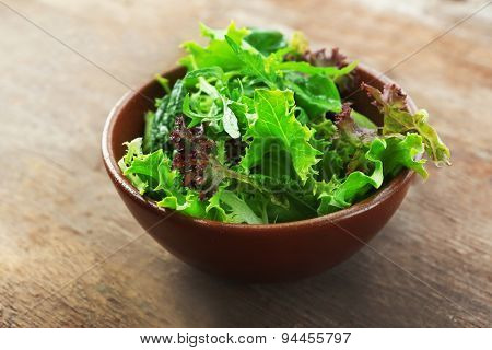 Bowl of mixed green salad on wooden background