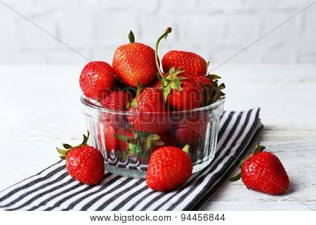 Ripe strawberries in glass saucer on napkin on wooden table, closeup
