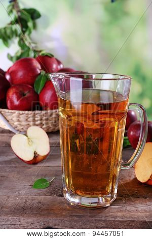 Full jug of apple juice and fruits on bright background