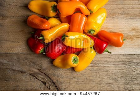 Colored Bell Peppers On A Weathered Wood Background.