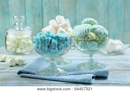 Sweet candies in glassware on napkin, closeup