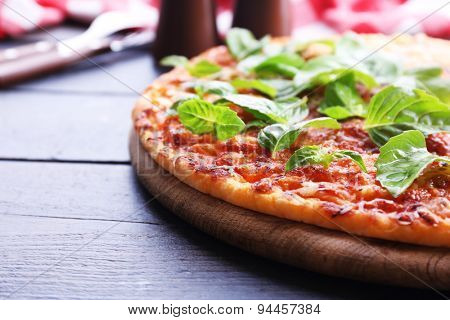 Pizza with basil on wooden table, closeup