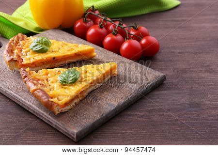 Slices of tasty cheese pizza with basil and vegetables on table close up