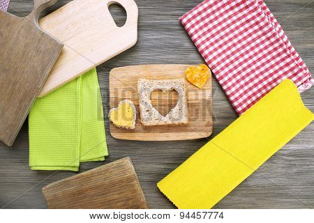 Bread slice with cut in shape of heart and cheese on table close up