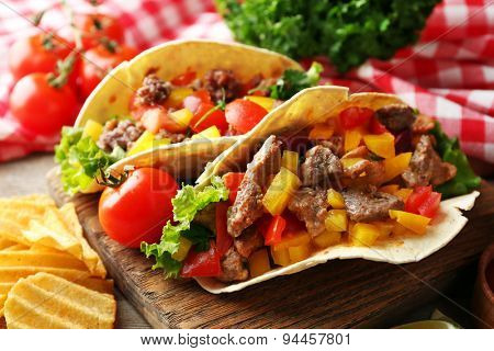 Homemade tasty burrito with vegetables and potato chips on cutting board, on wooden background