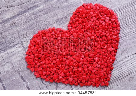Sugar sprinkles in heart shape on wooden background