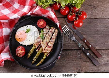 Dish of asparagus with eggs and bacon in pan on table, top view