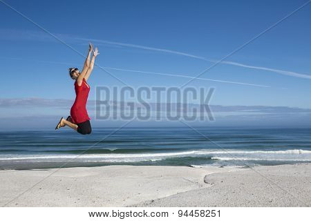Beautiful woman in red jumping with a beautiful beach in the back