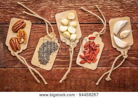 a variety of superfood (garlic, goji berry, chia seeds, macadamia and pecan nuts) on paper price tags against grunge barn wood background