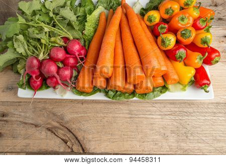 Fresh Carrots, Lettus, Bell Peppers, And Radishes On Weathered Wood Background.