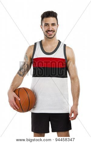 Athletic man holding a basket ball and smiling, isolated over a white background