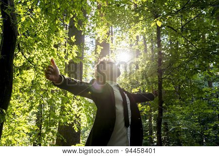 Businessman Standing With His Arms Outspread In Woodland