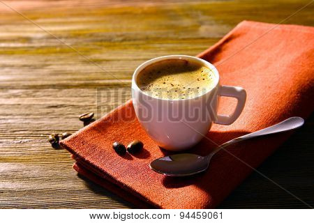 Cup of coffee on napkin on table close up