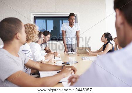 Businessman By Screen Addressing Boardroom Meeting