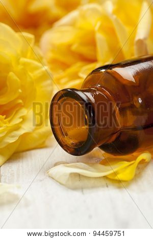 Apothecary bottle tilted in front of yellow rose blossoms
