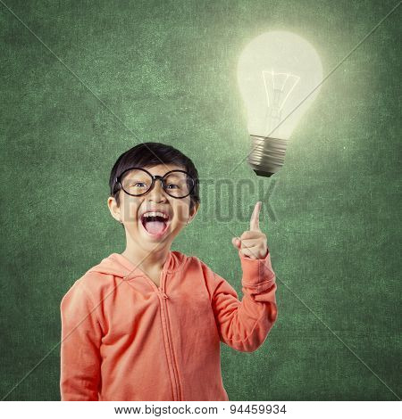 Brilliant Student Pointing At Bright Light Bulb