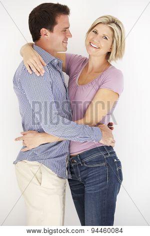 Studio Portrait Of Romantic Couple Embracing Against White Background