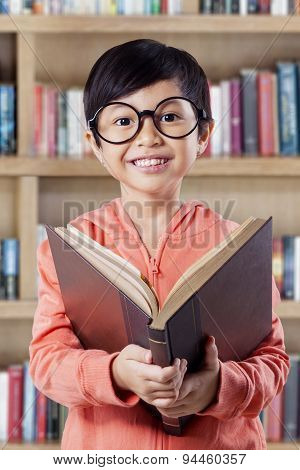 Cheerful Little Girl Studying With Book In Library
