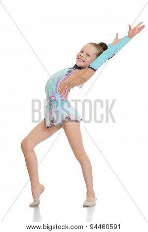 Girl gymnast doing exercises smiles