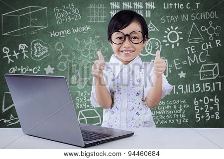 Child With Laptop Shows Ok Gesture In Class